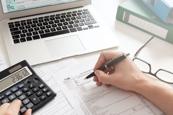 US Individual income tax return. Accountant working with US tax forms